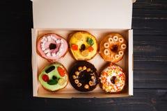 Farbige köstliche Schaumgummiringe in einem Kasten auf einem dunklen hölzernen Hintergrund lizenzfreie stockfotografie