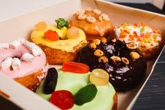 Farbige köstliche Schaumgummiringe in einem Kasten auf einem dunklen hölzernen Hintergrund stockbilder