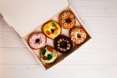 Farbige köstliche Schaumgummiringe in einem Kasten auf einem weißen hölzernen Hintergrund lizenzfreies stockfoto