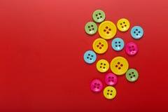 Farbige Knöpfe auf einer bunten Beschaffenheit des roten Hintergrundes Stockbild