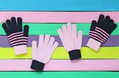 Farbige Knithandschuhe auf gemaltem hölzernem Hintergrund Lizenzfreies Stockfoto