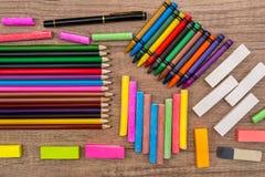 farbige Kreiden und Bleistifte auf einem hölzernen Hintergrund Stockbild
