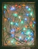 Farbige Lichter festliche Weihnachtsgirlande in einem alten Holzrahmen Lizenzfreie Stockfotos