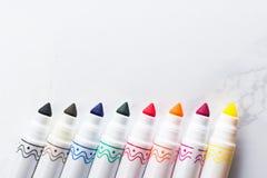 Farbige Markierungen in Folge vereinbart auf einer Marmortabelle Stockfotografie