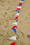 Farbige mit dem Kopfe stoßende Flaggen auf Sandoberfläche Lizenzfreie Stockfotos