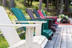 Farbige Muskoka-Stühle auf dem Dock Stockfoto