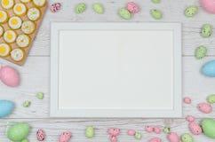 Farbige Ostereier über hölzernem Hintergrund mit Rahmen und Raum für Kopie, Text, Wörter Stockfotografie