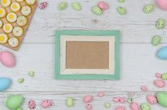 Farbige Ostereier über hölzernem Hintergrund mit Rahmen und Raum für Kopie, Text, Wörter Stockbild