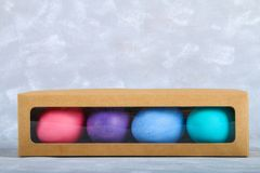 Farbige Ostereier in einer Geschenkbox auf einem grauen konkreten Hintergrund Stockbild