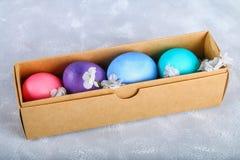 Farbige Ostereier in einer Geschenkbox auf einem grauen konkreten Hintergrund Stockbilder