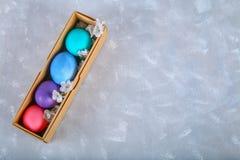 Farbige Ostereier in einer Geschenkbox auf einem grauen konkreten Hintergrund Stockfotos