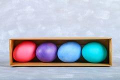 Farbige Ostereier in einer Geschenkbox auf einem grauen konkreten Hintergrund Lizenzfreies Stockbild