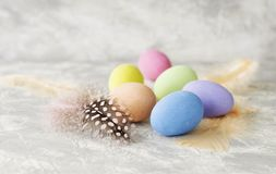 Farbige Ostereier mit Federn auf einer weißen Marmorierungtabelle, selektiver Fokus Lizenzfreies Stockbild
