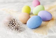 Farbige Ostereier mit Federn auf einer weißen Marmorierungtabelle, selektiver Fokus Lizenzfreie Stockfotografie
