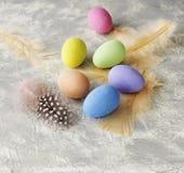 Farbige Ostereier mit Federn auf einer weißen Marmorierungtabelle, selektiver Fokus Stockbild
