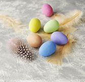 Farbige Ostereier mit Federn auf einer weißen Marmorierungtabelle, selektiver Fokus Lizenzfreies Stockfoto