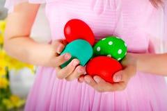 Farbige Ostereier sind in den Händen des Mädchens Stockfoto