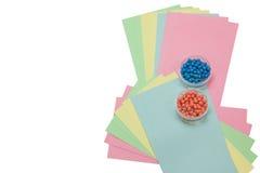 Farbige Papiere und Stifte lokalisiert Stockfotografie