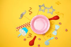 Farbige Partei, Bonbons und Konfettis auf Draufsicht des gelben Hintergrundes Stockfotos