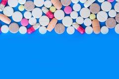 Farbige Pillen auf einem blauen Hintergrund Lizenzfreie Stockfotos