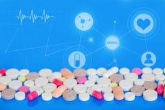Farbige Pillen auf einem blauen Hintergrund MEDIZINISCHES Konzept Stockfotos