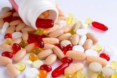 Farbige Pillen auf einer weißen Oberfläche Stockfotos