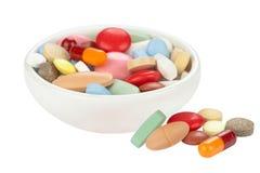 Farbige Pillen in der weißen Schüssel Stockfotos