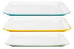Farbige Plastikservierplatten auf weißem Hintergrund lizenzfreie stockfotos