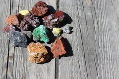Farbige raue Steine auf einem alten grauen hölzernen Brett Stockfoto
