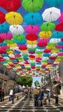Farbige Regenschirme verschoben über Einkaufsstraße Stockfotos