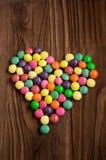 Farbige Süßigkeitstropfen in Form des Herzens Stockbilder