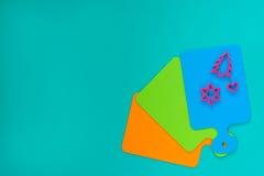 Farbige Schneidebretter ausgebreitet wie ein Fan und Formen für das Backen Stockfotos