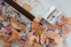 Farbige Schnitzel mit braunem Farbbleistift und -bleistiftspitzer in der Untertasse Lizenzfreie Stockfotos