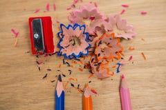 Farbige Schnitzel mit farbigen Bleistiften und Bleistiftspitzer Stockfoto