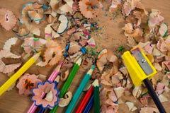 Farbige Schnitzel mit farbigen Bleistiften und Bleistiftspitzer Lizenzfreies Stockfoto