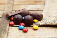 Farbige Schokoladenbonbons auf einem hölzernen Hintergrund Lizenzfreie Stockfotos