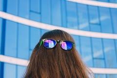 Farbige Sonnenbrillen am Nacken des Mädchens auf einem blauen Hintergrund Lizenzfreies Stockbild