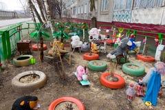 Farbige Spielwaren, Reifen und Puppen um ein Haus Lizenzfreies Stockfoto