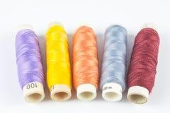Farbige Spulen des Threads auf weißem Hintergrund Stockfotos