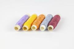 Farbige Spulen des Threads auf weißem Hintergrund Stockbilder