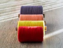 Farbige Spulen des Threads für das Nähen, Vorderansicht Stockfotos