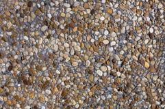 Farbige Steine auf grauer Wand Lizenzfreies Stockfoto