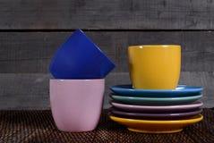 Farbige Tassen und Untertassen auf hölzernem Hintergrund Lizenzfreie Stockbilder