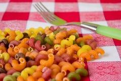Farbige Teigwaren lose auf der Tischdecke Lizenzfreies Stockbild