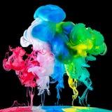 Farbige Tinten im Wasser auf schwarzem Hintergrund Lizenzfreies Stockfoto