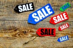Farbige Verkaufsaufkleber auf Draufsicht des dunklen hölzernen Hintergrundes Lizenzfreies Stockfoto