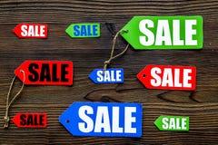 Farbige Verkaufsaufkleber auf Draufsicht des dunklen hölzernen Hintergrundes Stockfotografie
