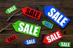 Farbige Verkaufsaufkleber auf Draufsicht des dunklen hölzernen Hintergrundes Stockfoto