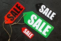 Farbige Verkaufsaufkleber auf Draufsicht des schwarzen Steinhintergrundes Lizenzfreies Stockbild