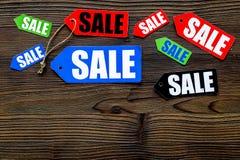 Farbige Verkaufsaufkleber auf dunklem hölzernem copyspace Draufsicht des Hintergrundes Stockbilder